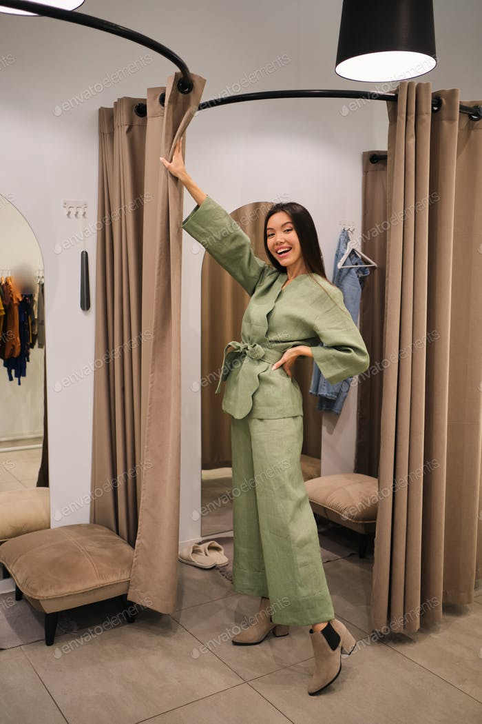Pretty cheerful Asian girl trying on stylish suit in dressing room of clothes store