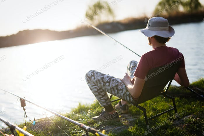 Men fishing in sunset and relaxing while enjoying hobby