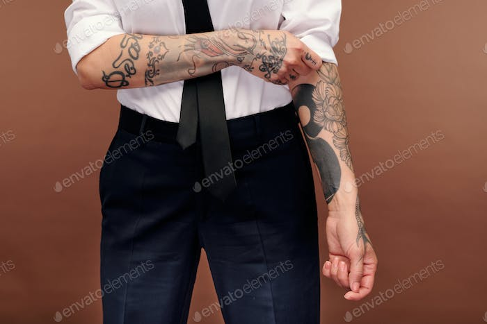 Masculine female in formalwear showing her arms covered with tattoos