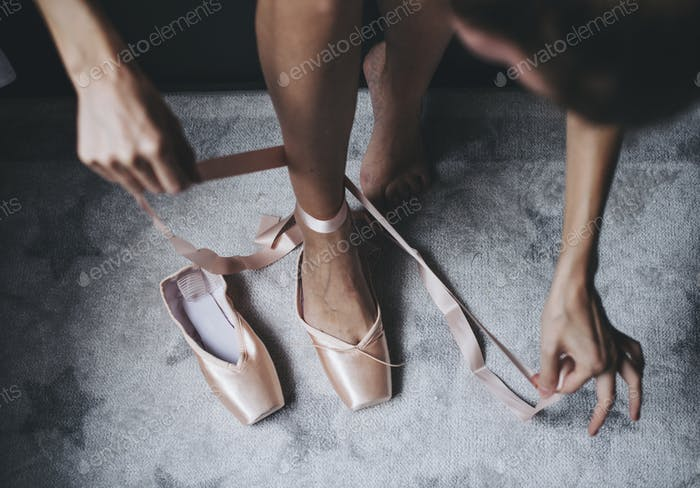 Putting on pink ballet shoes