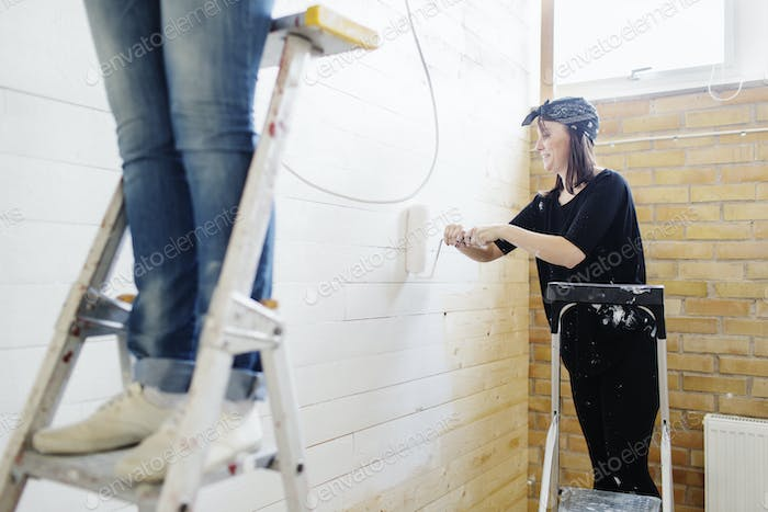 Woman painting wooden wall with paint roller