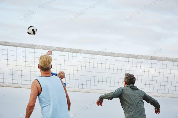 Mature men standing on a beach, playing beach volleyball.