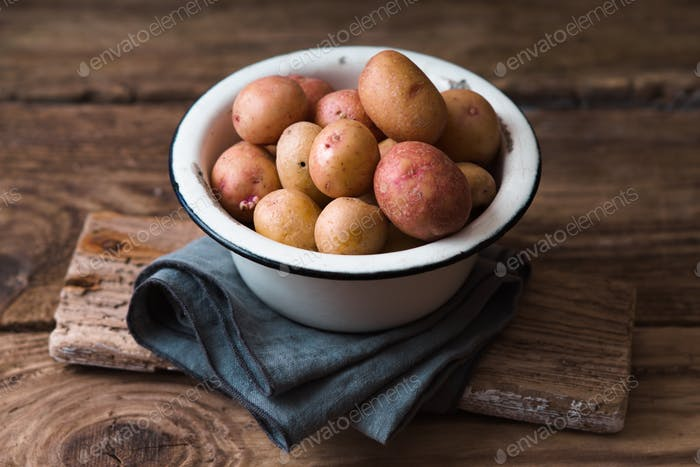 Raw potatoes in the metal bowl on the wooden table