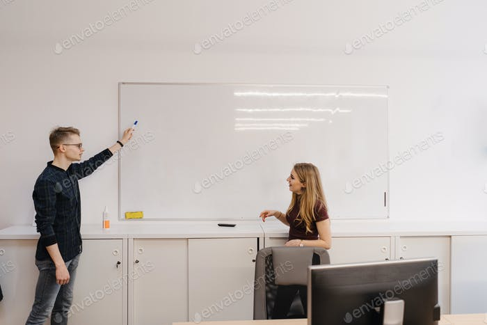 Young man discussing with colleagues over whiteboard at office