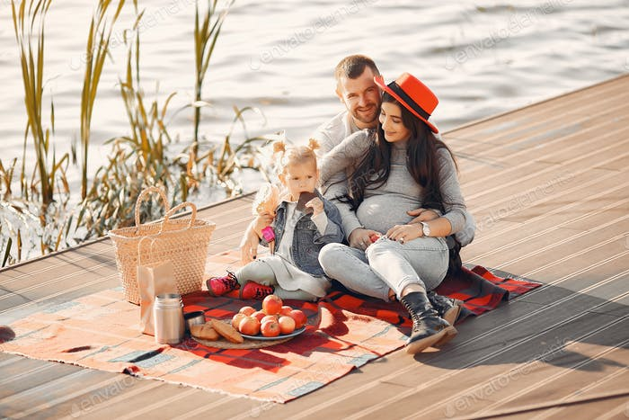 Family with little daughter sitting near water in a autumn park