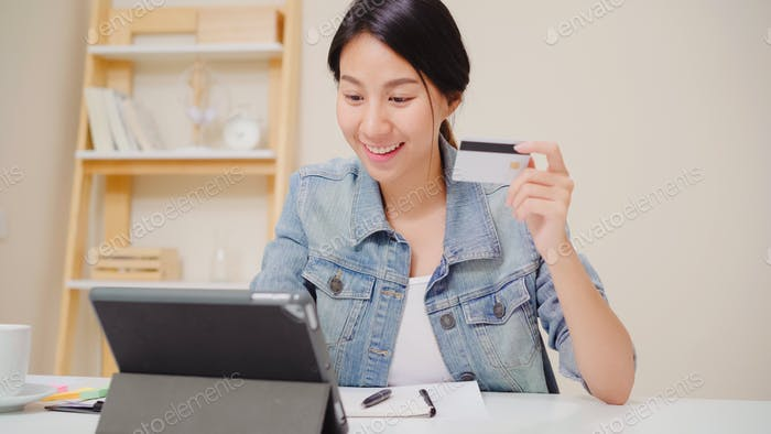 Asian woman using tablet buying online shopping by credit card.