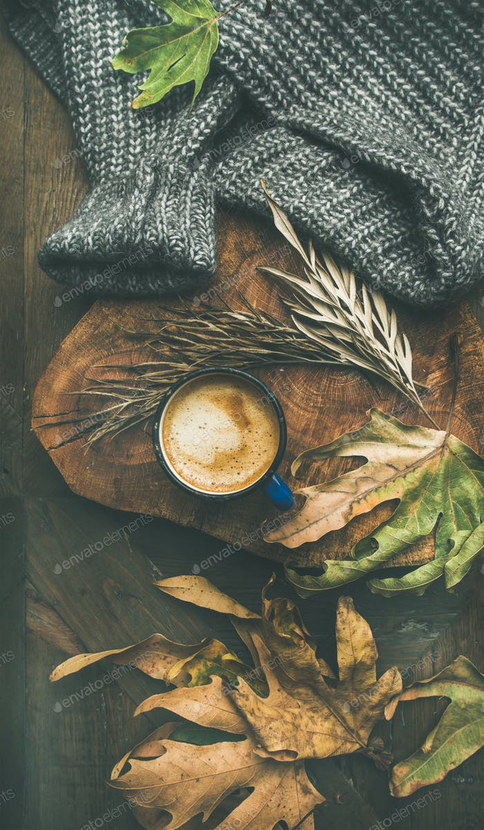 Autumn morning coffee concept with leaves and sweater, vertical composition