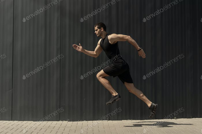 A side view shot of a fit young, athletic man jumping and runnin