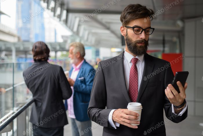 Three multi ethnic bearded businessmen together around the city