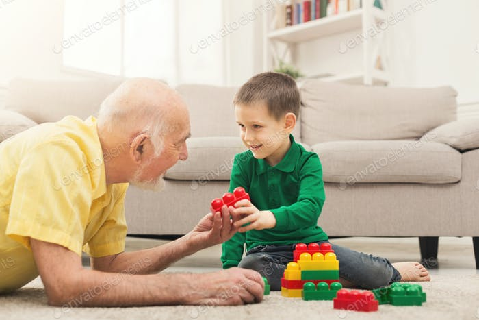 Boy playing with grandfather in building kit