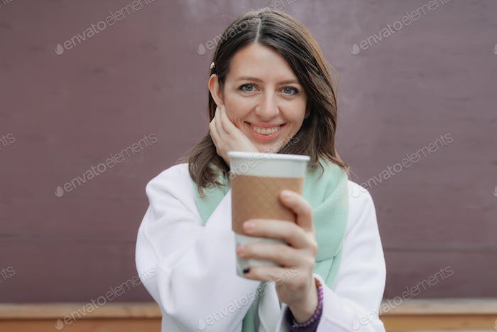 Smiling woman in winter coat with a coffee at the wall