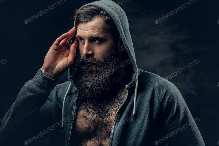 Bearded male with tattoo on a chest, dressed in a grey hoodie.