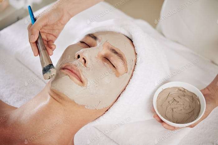 Cosmetologist applying purifying clay mask