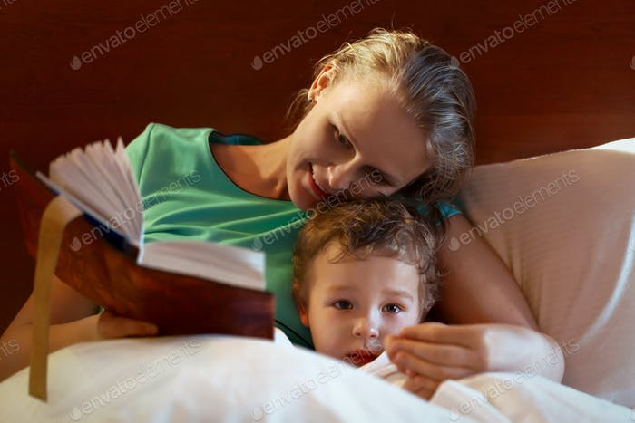 Young mother reading to her child in bed
