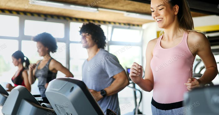 Group of people exercising in a gym cardio training and running