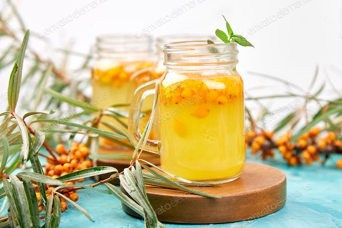 Colorful hot sea buckthorn tea with ginger and honey