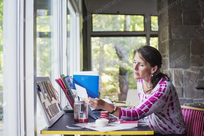 Woman sitting at a desk at home, working.