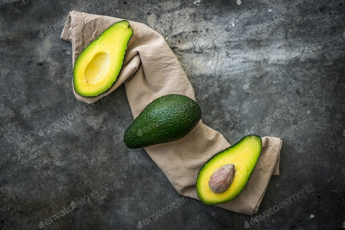 Organic avocado on black rustic background