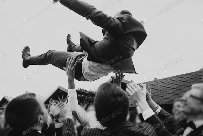 Men tossing up groom at stylish wedding reception