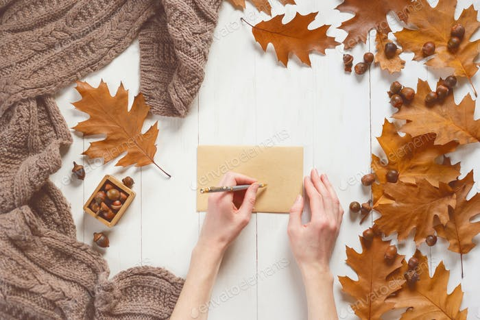 Woman's hands sign an envelope with a greeting card. Top view. Autumn time concept