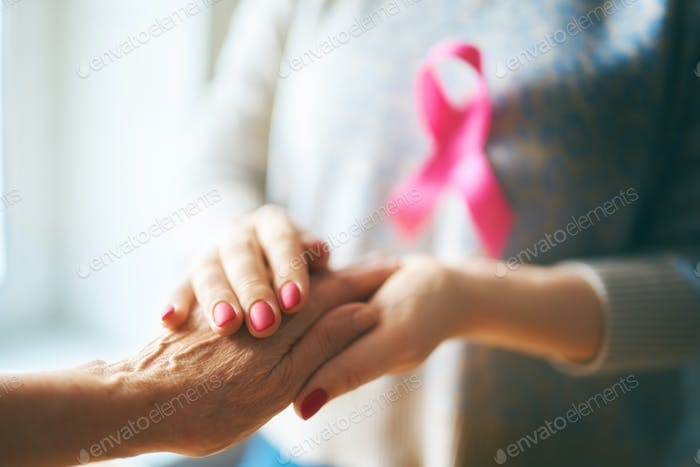 Females hands and symbol of Breast Cancer Awareness