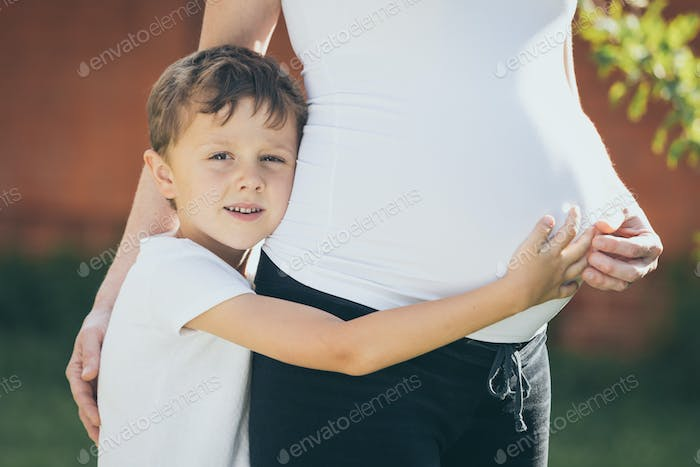 Happy little boy huging mother in the park at the day time.