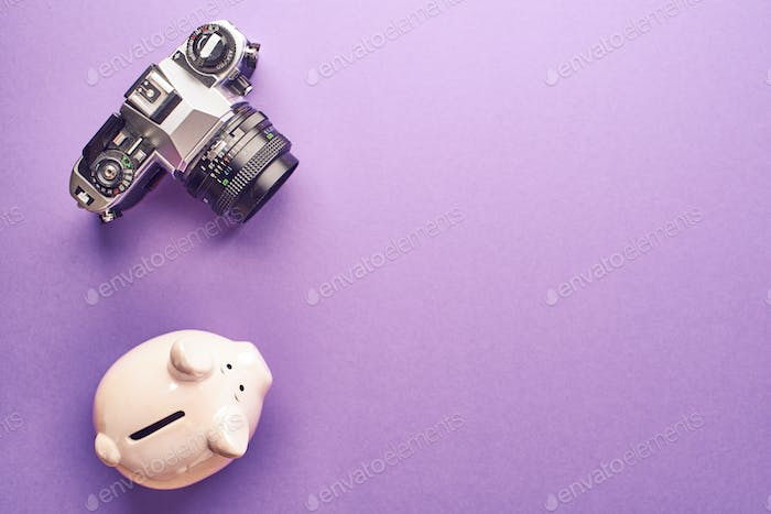 Piggy bank and film camera on an white table