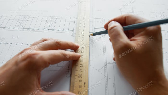 Male hands drawing a construction plan