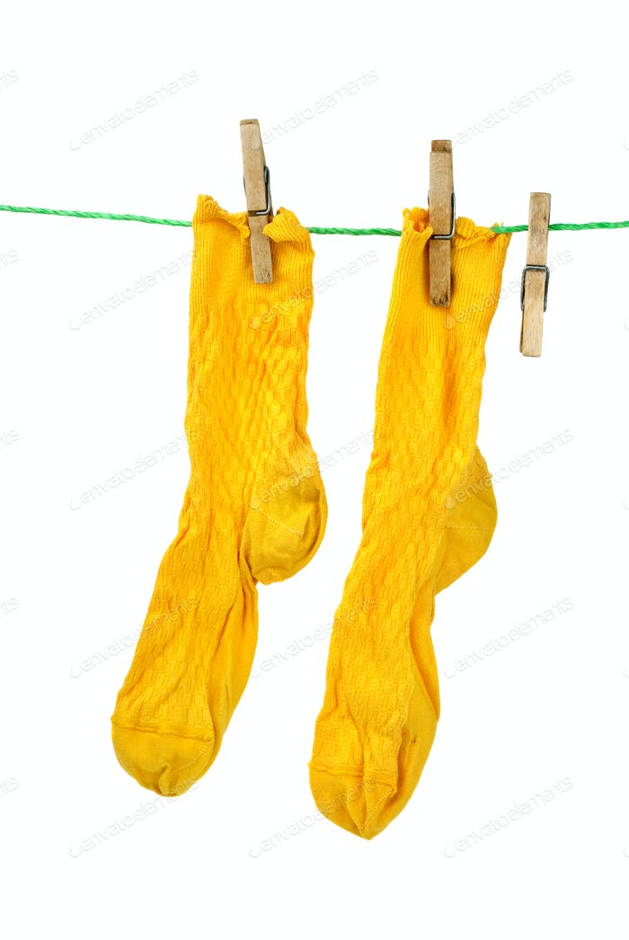 Pair of yellow socks hanging on the rope