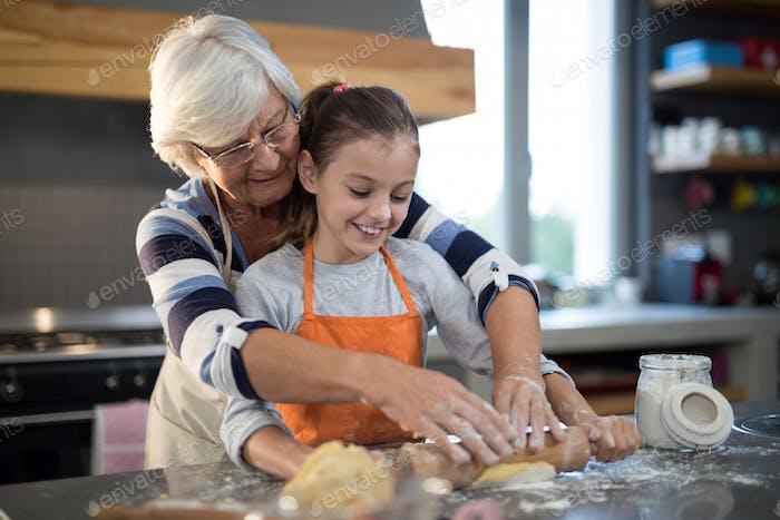 Grandmother helping granddaughter to flatten dough
