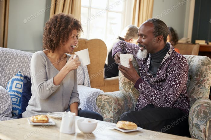 Middle Aged Couple Sitting Around Table In Coffee Shop