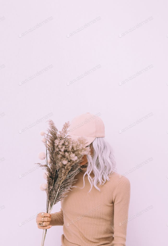 Stylish blonde girl with autumn decor bouquet in white space.