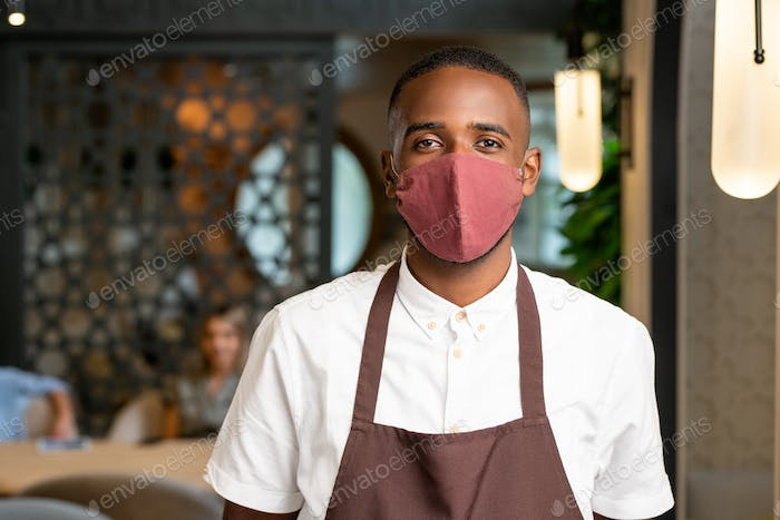 Young waiter of African ethnicity in apron and protective mask working in cafe