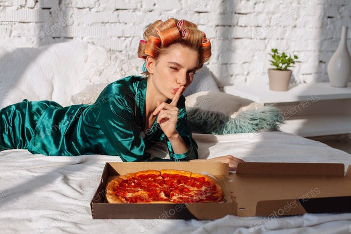 young female with finger near lips with pizza box pizza in bed