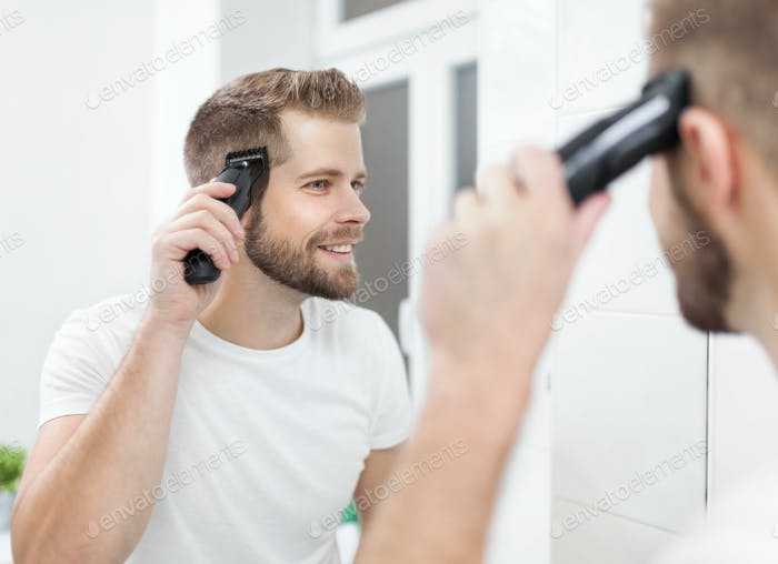 Handsome man cutting his own hair with a clipper