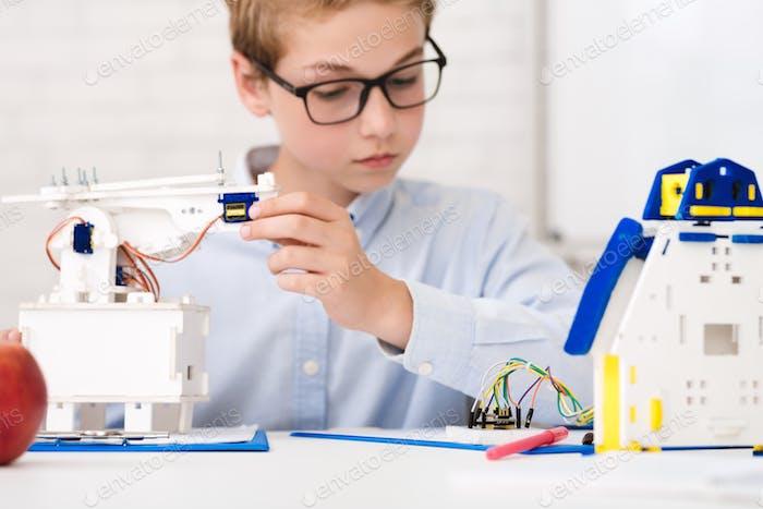 Smart schoolboy at stem lesson constructing robots