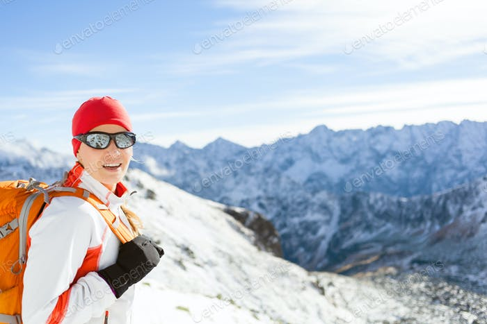 Happy Girl Hiking in Winter High Mountains with Backpack