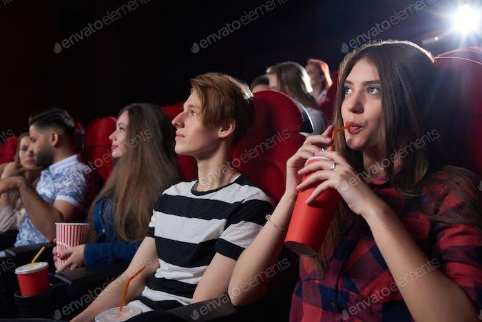 Freunde sehen interessante Filme im großen Kinosaal
