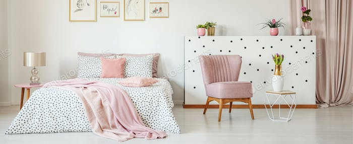 Dotted bedding on double bed placed in white room interior with