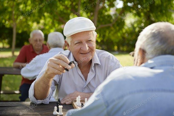 Aktive pensionierte Senioren, zwei alte Männer spielen Schach im Park