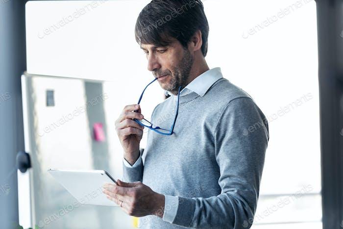 Элегантный бизнесмен работает с цифровым планшетом в офисе.