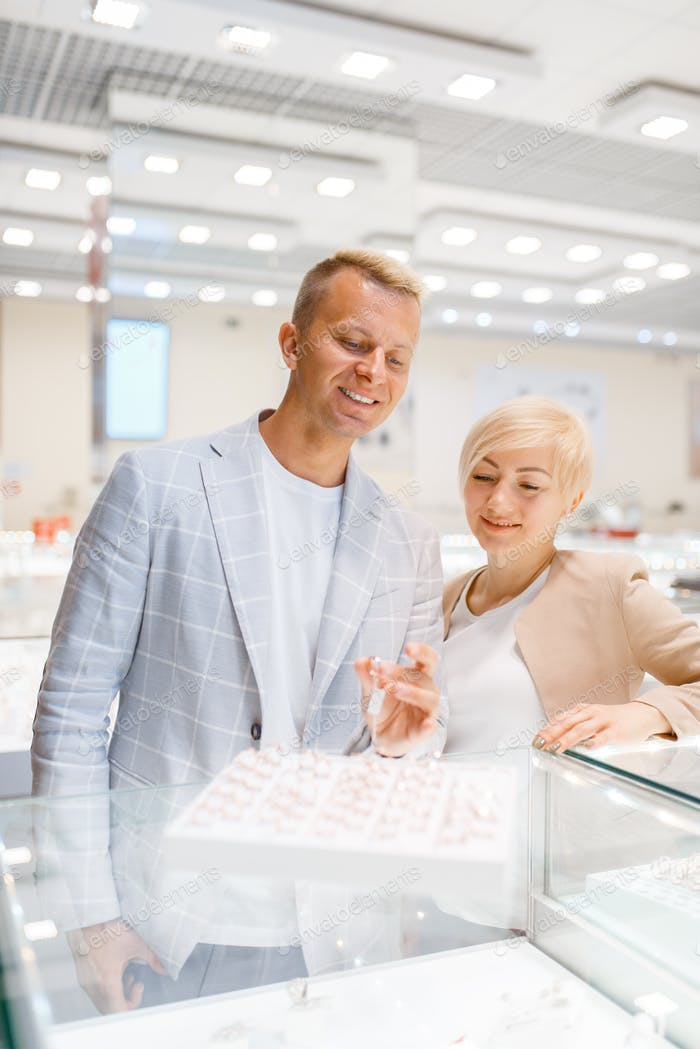 Love couple choosing wedding rings, jewellery shop