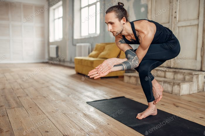 Male yoga doing balance exercise on mat in gym