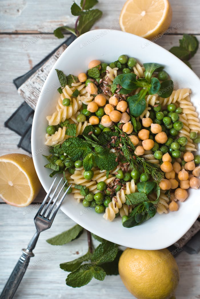Salad with fusilli, chickpeas, grass in a white ceramic bowl