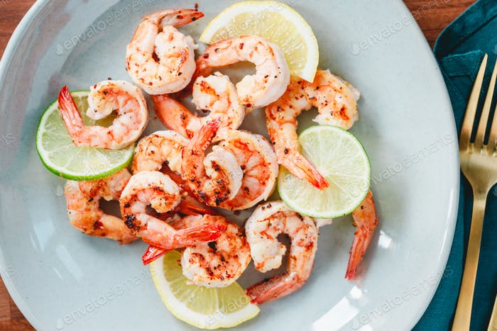 Fried tiger shrimp with lime, lemon and spices on a ceramic dish.