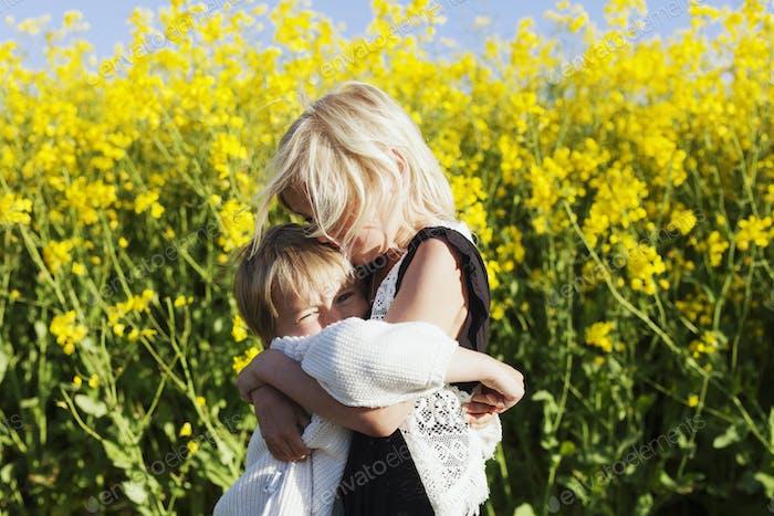 Mädchen umarmen Bruder auf Rapsfeld