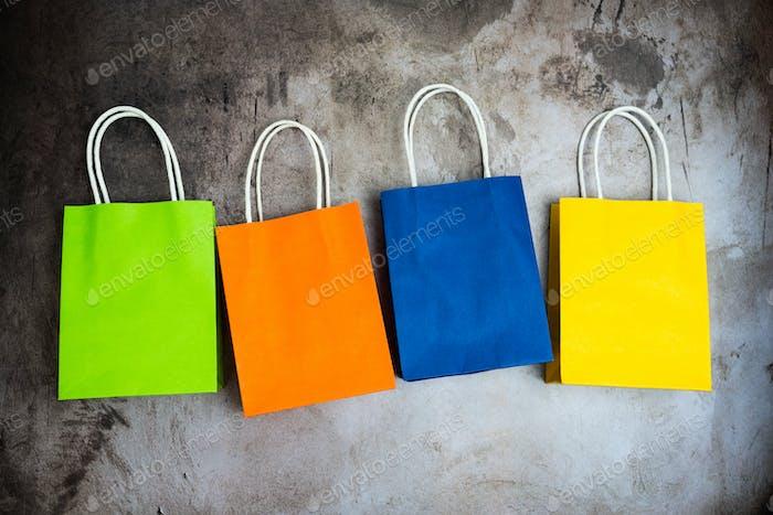cuatro bolsas de compras de colores en una fila