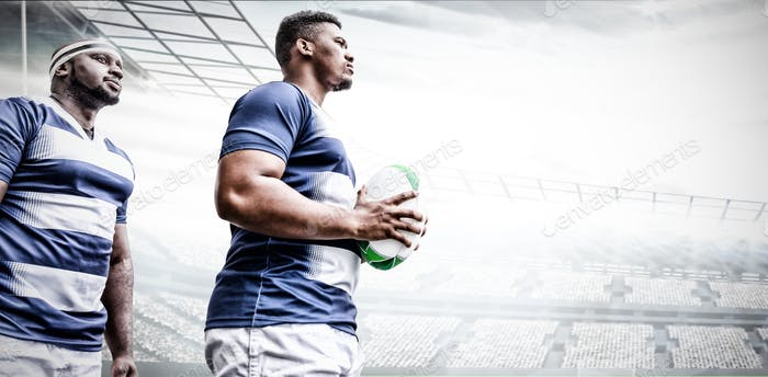 Digital composite image of two rugby players holding ball in sports stadium
