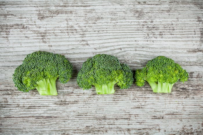 Fresh raw organic broccoli on a wooden background
