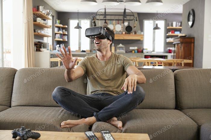 Man Sitting On Sofa Wearing Virtual Reality Headset